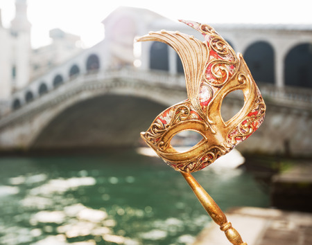 Ultimate getaway shortcut - start New Year going on Carnival in Venice, Italy. Closeup on woman hand holding Venice Mask in the front of Rialto Bridge