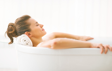 Foto de Portrait of young woman relaxing in bathtub - Imagen libre de derechos