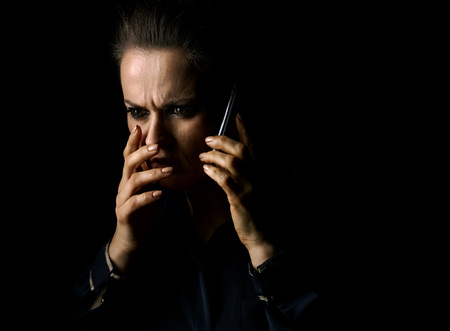 ?oming out into the light. Portrait of stressed woman in the dark dress isolated on black background speaking on a smartphone