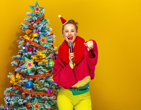 Festive season. smiling young woman in colorful clothes near Christmas tree on yellow background with microphone singing and pointing at camera