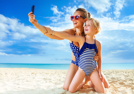 Foto de Sun kissed beauty. smiling healthy mother and daughter in beachwear on the seacoast with digital camera taking selfie - Imagen libre de derechos