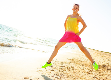 Colorful and wonderfully cheerful mood. Full length portrait of young woman in colorful dress on the beach in the evening jumping