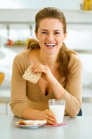 Smiling young woman having healthy breakfast