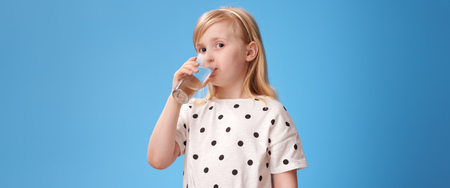 Foto de modern child in red pants drinking glass of water on blue background - Imagen libre de derechos