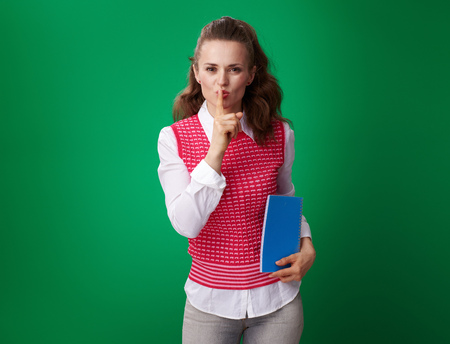 modern student woman in a red waistcoat with a blue notebook showing shh gesture isolated on green