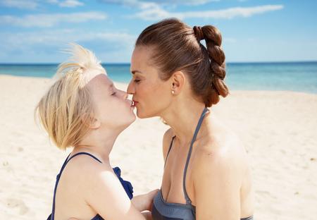 Foto de Modern mother and daughter in swimsuit on the seacoast kissing - Imagen libre de derechos
