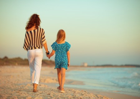 Foto de Seen from behind stylish mother and daughter on the seacoast in the evening walking - Imagen libre de derechos