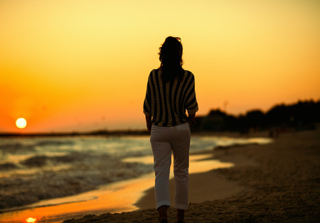 Foto de Seen from behind stylish woman on the beach in the evening walking. Stroll on the beach - a great way to get away from the busy everyday life - Imagen libre de derechos