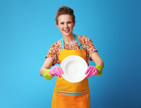 smiling young housewife in orange apron showing washed plate against blue background. Who better washing dishes - a housewife or a dishwasher?の写真素材