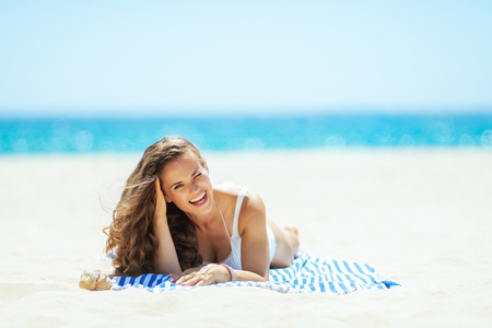 Foto de smiling fit woman in white swimwear on the seashore lying on a striped towel. getting vitamin D after long winter months. total relaxation on the best beach vocation. Sun protected hair. - Imagen libre de derechos