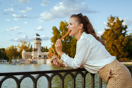 Photo pour happy modern tourist woman in white blouse and shorts in Madrid, Spain eating traditional Spain churro. churros - classic Madrid sweet snack. woman travel alone. perfect destination choice.solo travel - image libre de droit