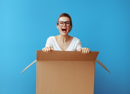 Photo pour smiling young woman in white t-shirt get out of a cardboard box against blue background - image libre de droit