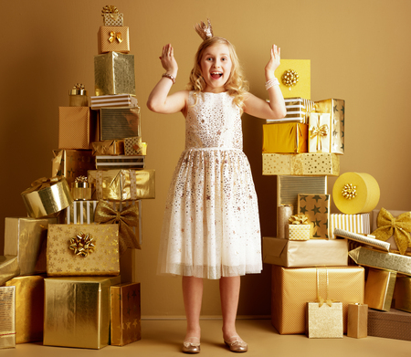 Full length portrait of surprised elegant child in beige fit and flare dress and a little crown on head among 2 piles of golden gifts in front of a plain wall open her eyes. unique birthday gifts.