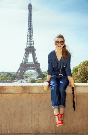 Photo pour Portrait of happy trendy tourist woman in blue jeans overall with coffee cup and baguette having excursion against clear view of the Eiffel Tower in Paris, France. - image libre de droit