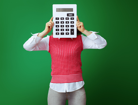 modern student in grey jeans and pink sleeveless shirt hiding behind big white calculator isolated on green. Finances and expenditures of modern education.