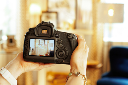 Closeup on modern DSLR camera in hand of modern female interior photographer at home.
