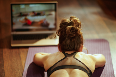 Photo pour Seen from behind fit sports woman in fitness clothes in the modern living room using online fitness training program in laptop while laying on fitness mat. - image libre de droit
