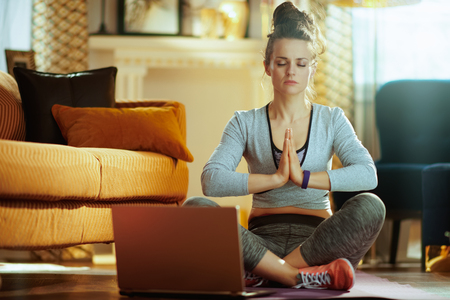 Foto de relaxed fit sports woman in fitness clothes in the modern house meditating using online yoga training program in laptop. - Imagen libre de derechos