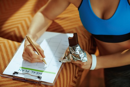 Foto de Closeup on young woman in fitness clothes with chocolate raw protein bar filling meal plan in the modern house. - Imagen libre de derechos