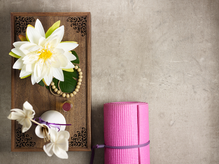 Foto de Closeup on tray with fragrant stuff for aroma yoga, beads and pink yoga mat laying on the floor. - Imagen libre de derechos