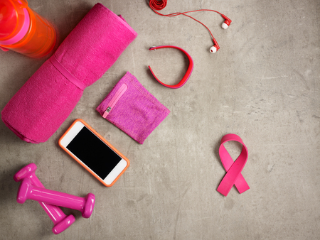 Photo pour Closeup on laying on the floor pink dumbbells, towel, bottle of water, headphones, fitness tracker, armlet, smartphone and pink ribbon shaped elastic band. - image libre de droit