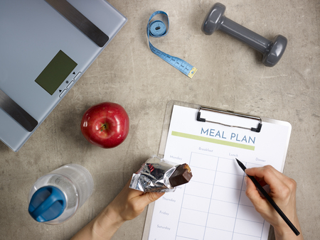 Foto de Closeup on weight scales, grey dumbbell, red apple, bottle of water, tape measure laying on the floor and female hands with bitten raw protein bar filling meal plan. - Imagen libre de derechos