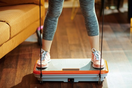 Photo for Closeup on fit sports woman in fitness clothes at modern home training using vibration power plate. - Royalty Free Image