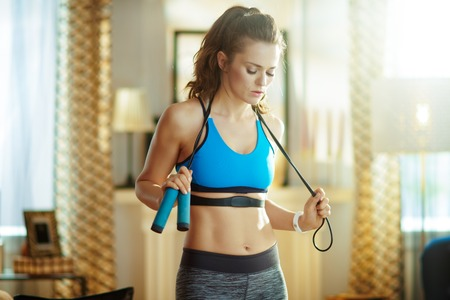 young woman in fitness clothes with a jump rope and heart rate monitor catching breath after exercise in the modern house.