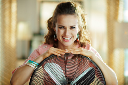 Photo for Portrait of smiling stylish housewife with metallic floor standing fan in the modern living room in sunny hot summer day. - Royalty Free Image
