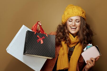 Photo pour Hello autumn. happy young woman in yellow beret and scarf with credit card, purse and shopping bags isolated on beige. - image libre de droit