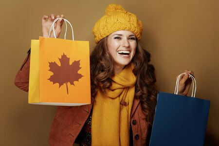 Photo pour smiling young woman in yellow beret and scarf showing autumn shopping bags on brown background. - image libre de droit