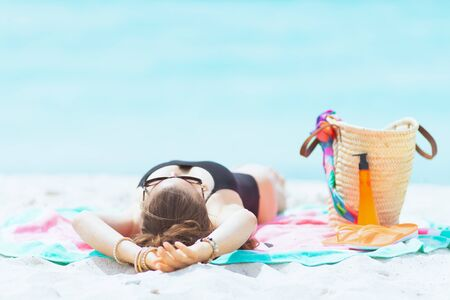 Photo for elegant middle age woman with long curly hair in elegant black swimsuit on a white beach sleeping while sun tanning. - Royalty Free Image