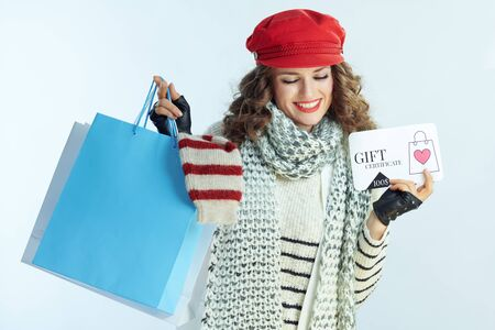 Photo pour happy elegant 40 years old woman with long brunette hair in sweater, scarf and red hat showing shopping bags with sweaters and discount coupon against winter light blue background. - image libre de droit