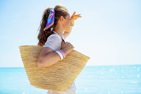 Photo pour healthy woman in white t-shirt with beach straw bag looking into the distance on the seacoast. - image libre de droit