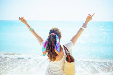 Photo pour Seen from behind trendy 40 year old woman in white t-shirt with beach straw bag with open arms rejoicing on the seashore. - image libre de droit