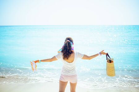 Photo pour Seen from behind trendy woman in white t-shirt with beach straw bag and orange flip flops with raised arms rejoicing on the seacoast. - image libre de droit