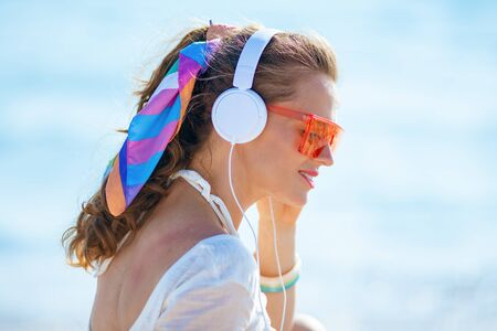 Photo pour Side view of relaxed modern woman in white t-shirt and pink shorts listening to the music with headphones on the ocean shore. - image libre de droit