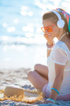 Photo pour smiling healthy woman in white t-shirt and pink shorts listening to the music with headphones on the seacoast. - image libre de droit
