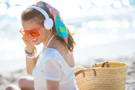 Photo pour happy trendy woman in white t-shirt and pink shorts listening to the music with headphones on the ocean shore. - image libre de droit