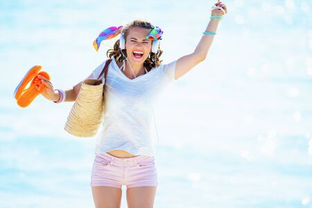 Photo pour happy trendy 40 year old woman in white t-shirt and pink shorts with beach straw bag listening to the music with headphones and jumping on the seashore. - image libre de droit