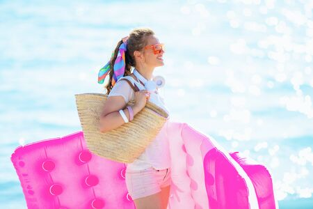 Photo pour happy modern 40 year old woman in white t-shirt and pink shorts with beach straw bag on the ocean coast looking into the distance while holding inflatable mattress. - image libre de droit