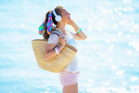 Photo pour relaxed modern 40 year old woman in white t-shirt and pink shorts with beach straw bag listening to the music with headphones on the ocean shore. - image libre de droit