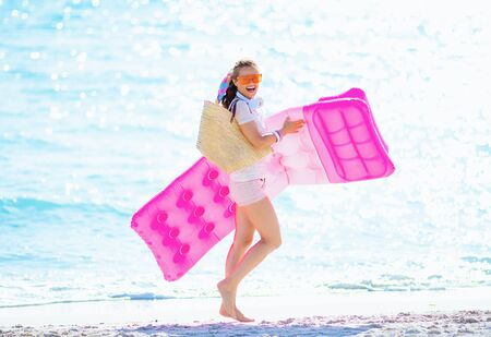 Photo pour happy modern middle age woman in white t-shirt and pink shorts with beach straw bag on the seacoast holding inflatable mattress and walking. - image libre de droit