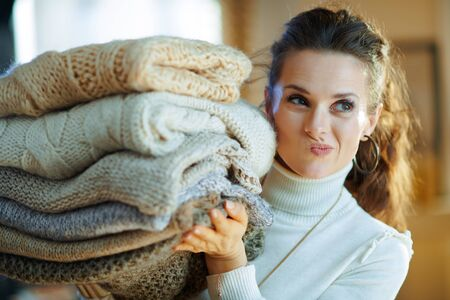 Photo pour doubting stylish 40 years old woman in white sweater and skirt at modern home in sunny winter day holding pile of sweaters. - image libre de droit