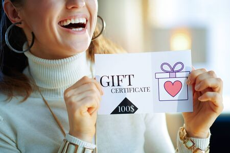 Photo pour Closeup on smiling modern 40 years old woman in white sweater and skirt at modern home in sunny winter day holding gift certificate. - image libre de droit