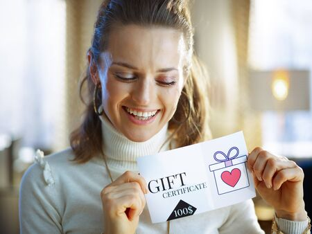 Photo pour smiling middle age woman in white sweater and skirt with gift certificate at modern home in sunny winter day. - image libre de droit