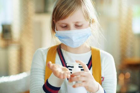 Photo for modern girl in white striped t-shirt with medical mask and backpack sanitizes hands with a disinfectant in the modern living room in sunny day. - Royalty Free Image