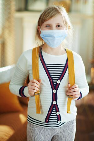 Photo for young child in white striped t-shirt with medical mask and backpack at modern home in sunny day. - Royalty Free Image