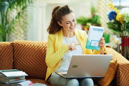 Photo pour happy modern middle age woman in jeans and yellow jacket showing textbook during a video conference with a teacher on a laptop in the modern house in sunny day. - image libre de droit