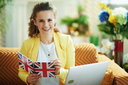 Photo pour smiling elegant middle age housewife in jeans and yellow jacket with laptop taking notes with a pen in a UK flag notebook at modern home in sunny day. - image libre de droit